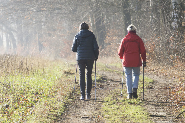 Rear view of two women practicing nordic walking