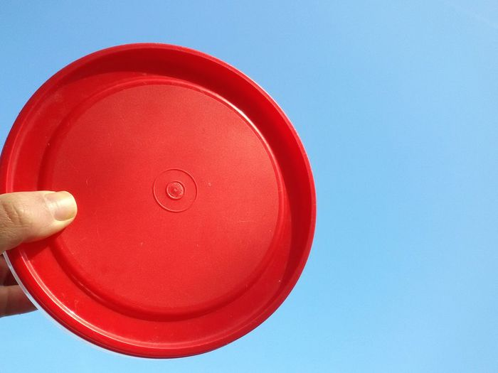 Cropped hand holding red plastic container against clear sky