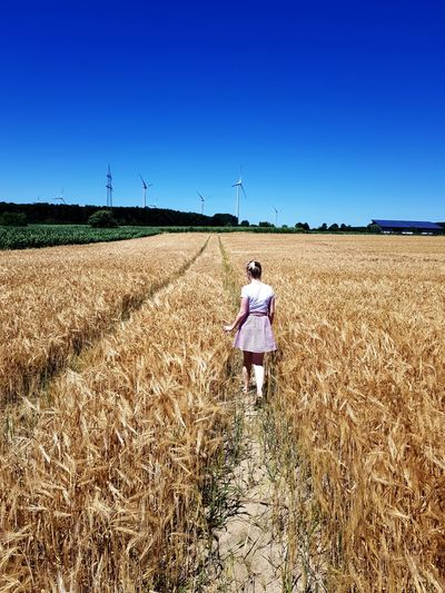 Rear view of woman walking on agricultural field against clear sky