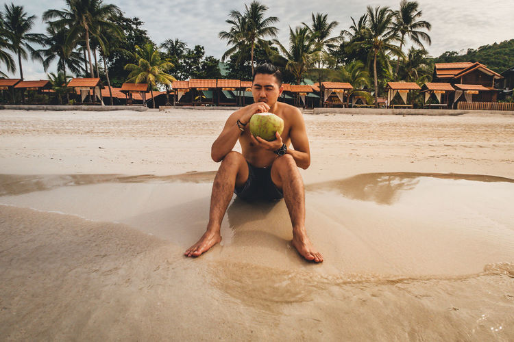 Full Length Of Shirtless Man Drinking Coconut Water While Sitting On Shore At Beach