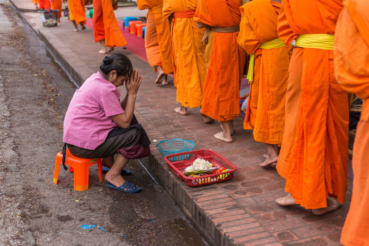 Side view of woman with hands clasped greeting monks standing in row