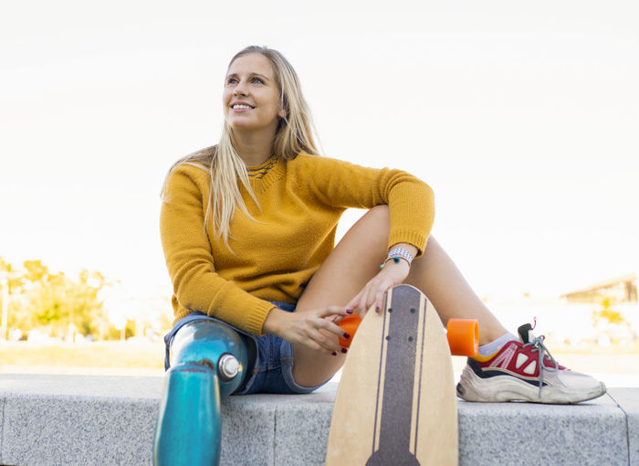 Smiling young woman sitting against clear sky