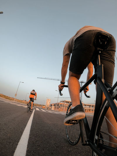 Rear view of man riding bicycle on road against clear sky