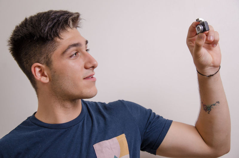 Portrait of young man holding camera against gray background