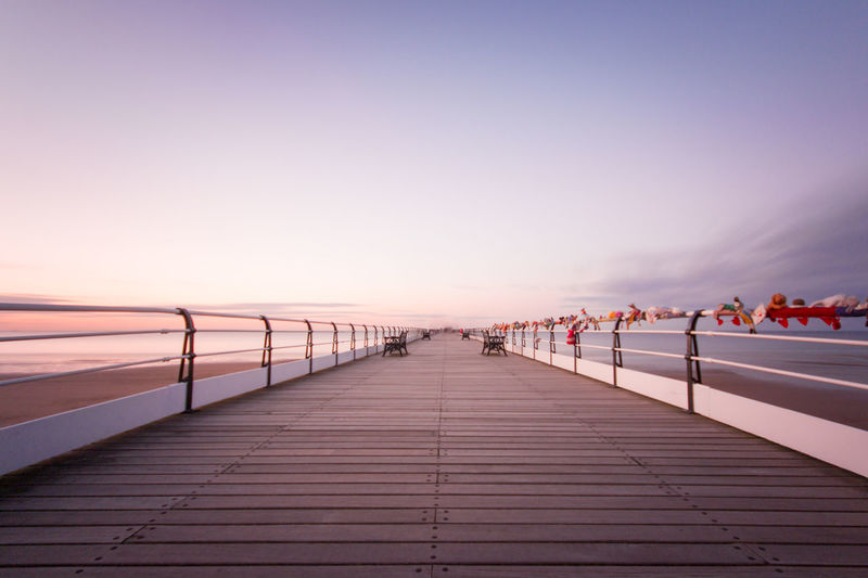 Beach Beauty In Nature Boardwalk Calm Clear Sky Copy Space Diminishing Perspective Dusk Nature Ocean Outdoors Pier Pier Scenics Sea Sky Sunset Surface Level The Way Forward Tranquil Scene Tranquility Water