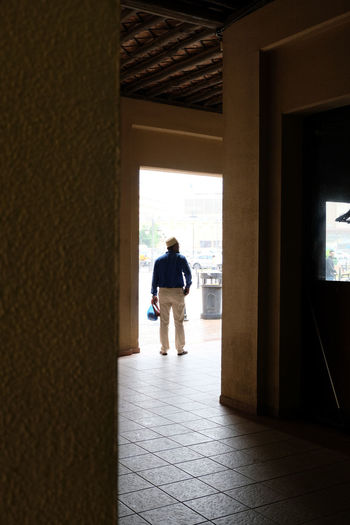 Rear view of man standing at entrance of building
