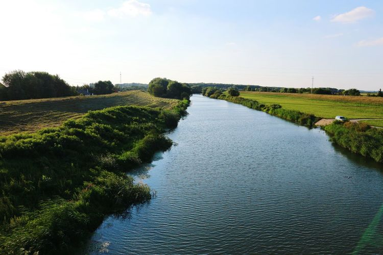High angle view of river amidst green landscape against sky