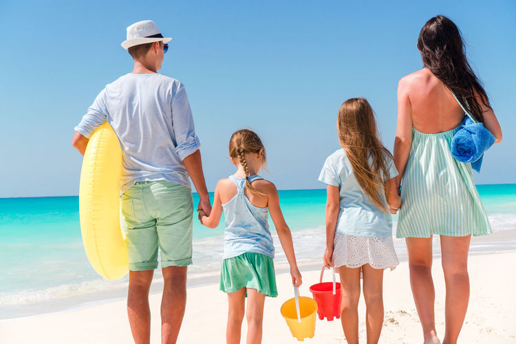 Rear view of family standing on beach