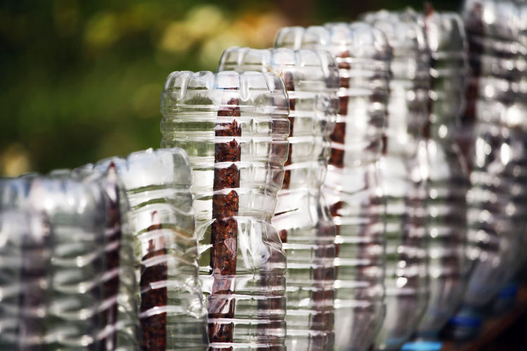 Empty plastic bottles on a garden fence. Gardening Abundance Arrangement Blister Pack Bottle Business Close-up Day Focus On Foreground Food And Drink Glass - Material In A Row Large Group Of Objects No People Order Pattern Plastic Recycle Repetition Retail  Selective Focus Silver Colored Stack Transparent