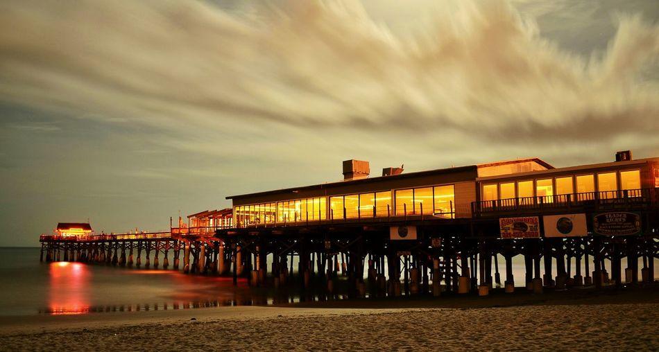 Illuminated stilt structure and calm sea at dusk