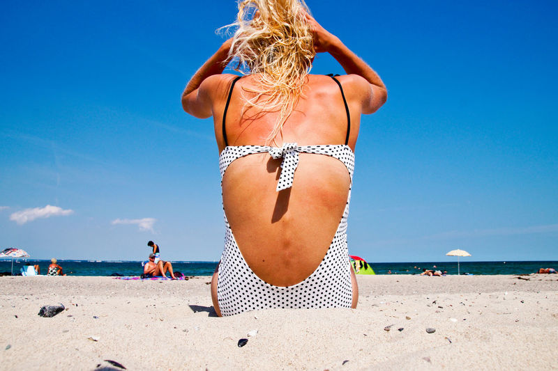 Rear view of woman siting on sand at beach against sky