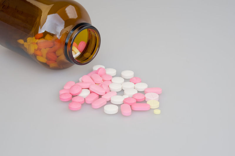 Colorful tablets and brown bottle place on a white background. Care Container Copy Space Doctor  Drug Medicine Pharmacy Pink Stack Tablet Therapy Background Bottle Brown Dose Health Healthy Medical Pill Still Life Studio Shot Treatment White Yellow