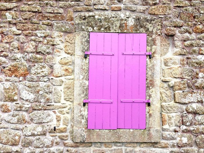 Close-up of pink window on wall