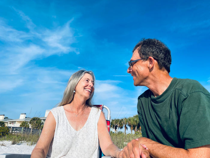 Senior man and woman smiling and looking with love at one another as they sit under blue sky