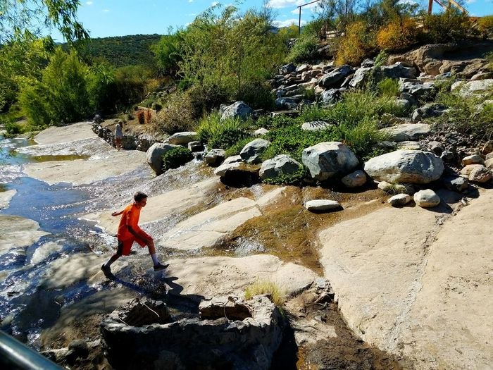Fun little oasis in the desert! Two Children Playing Constructed Waterfall Stream Sunlight Leisure Activity Real People Trees And Sky Outdoors Day Nature