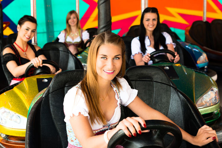 Portrait Of Happy Women Wearing Dirndl While Enjoying In Bumper Cars