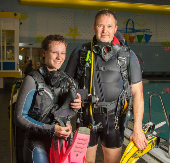Portrait of people wearing diving equipment standing on poolside