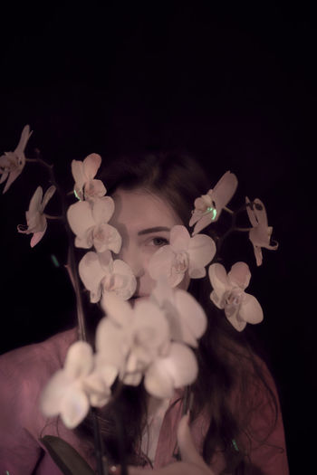 Portrait of woman holding white flowers against black background