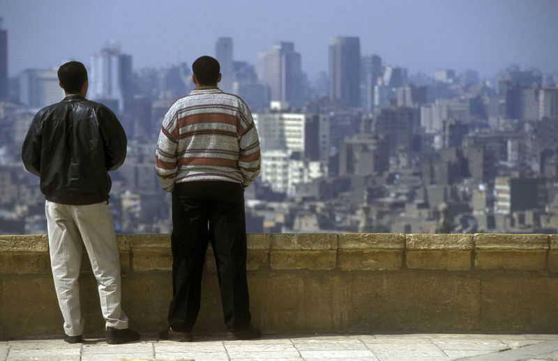 Rear view of men standing by railing against city buildings