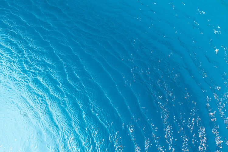 View of surface of turquoise water in swimming pool, sea or ocean, summer background. gradient