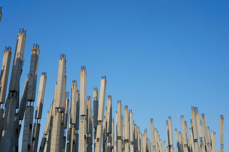 Low angle view of fence against clear blue sky