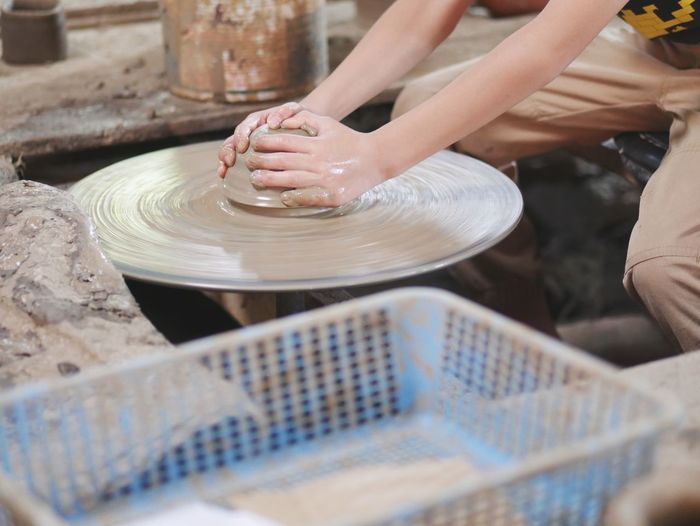 Midsection Of Person Making Pot On Pottery Wheel