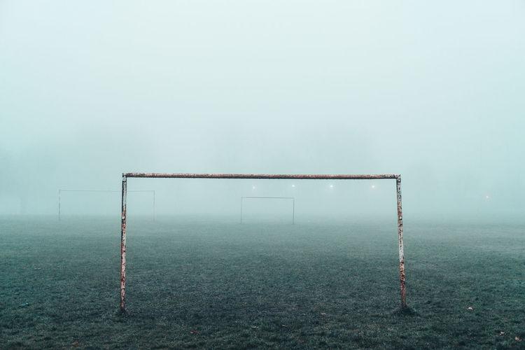 A football goalpost sits in a foggy park.