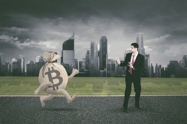 Digital composite image of bitcoin symbol walking towards businessman in city