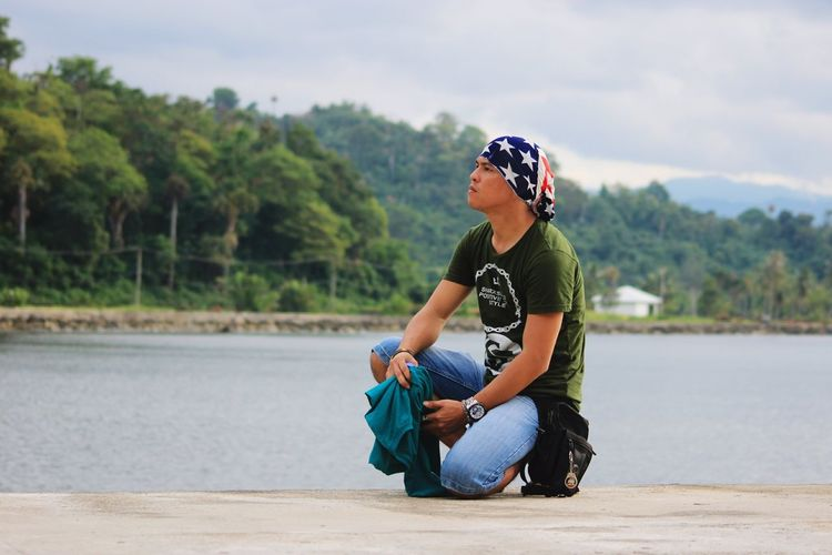 Side view of senior man sitting by lake against sky