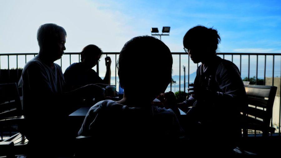 Silhouette family having breakfast in balcony