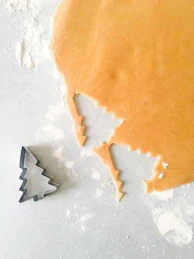 Directly Above Shot Of Christmas Tree Pastry Cutter With Dough On Table