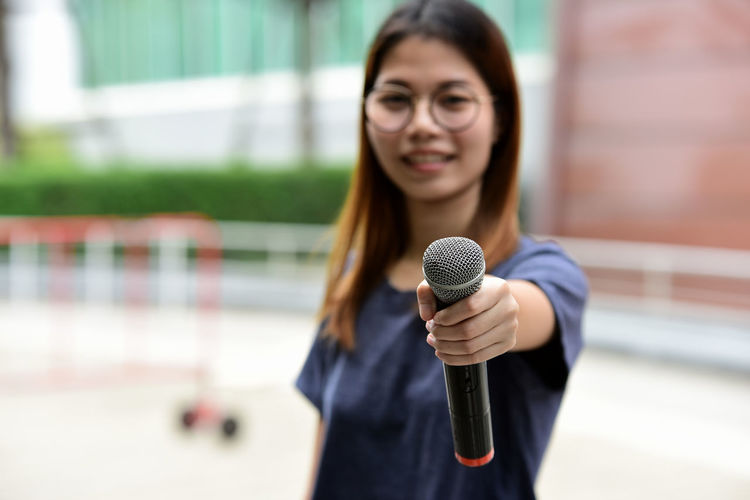 Portrait of female journalist with microphone standing against building