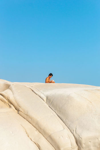 Mid distance view of man sitting against clear blue sky