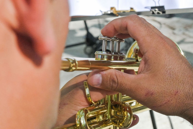 Midsection Of Street Musician Playing Trumpet On Street