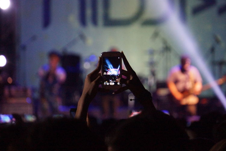 People Photographing Through Smart Phone At Concert