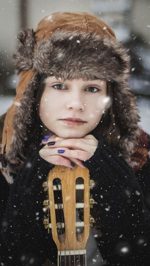 Portrait Of Woman With Guitar During Snowfall