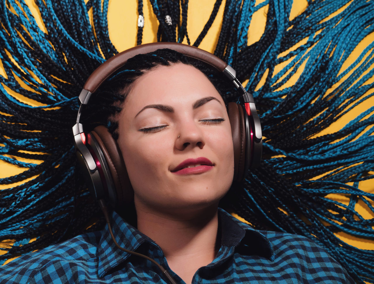 Close-Up Of Young Woman With Braided Hair Listening To Music Against Yellow Background