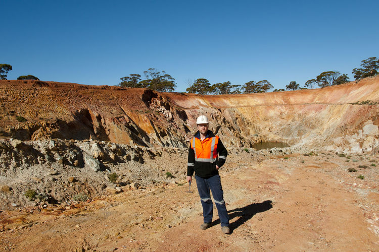 Worker standing by rock formation against clear sky