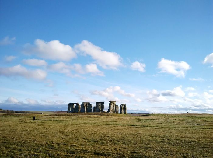 Scenic view of stonehenge on field against sky