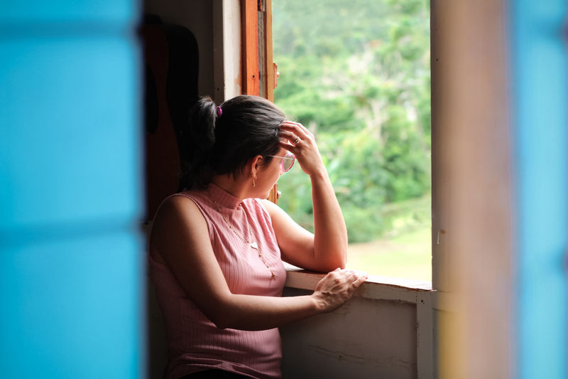 Woman looking away while sitting on window at home