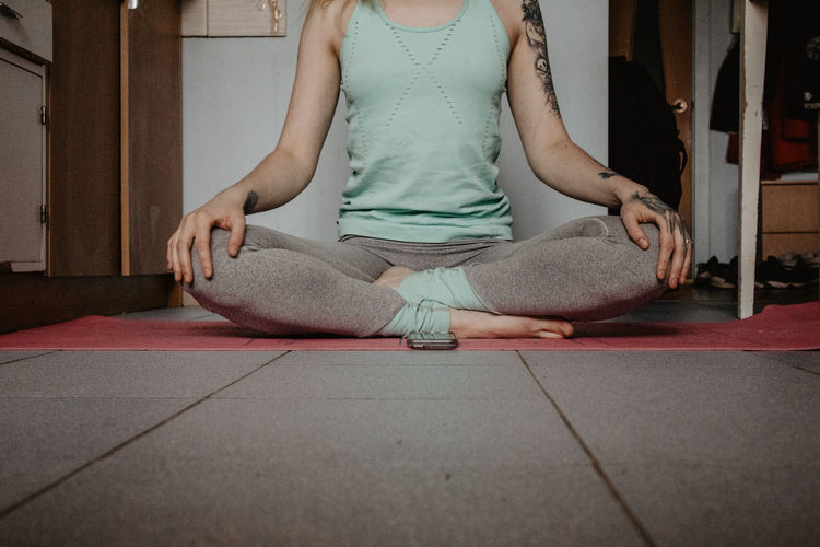 Low Section Of Woman Meditating While Sitting At Home