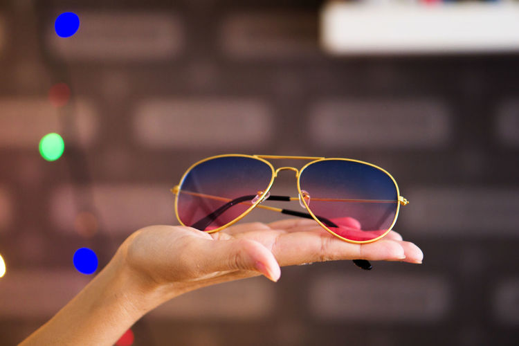 Close-up of hand holding sunglasses