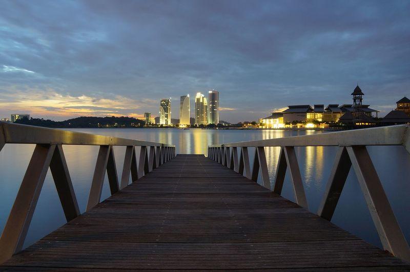Bridge over river amidst buildings against sky at dusk