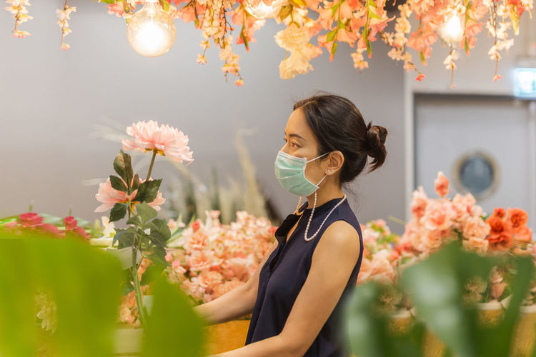Woman in medicail mask chooses artificial flowers in flower shop
