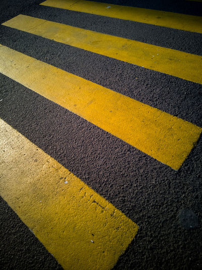 Yellow crossing sign on road