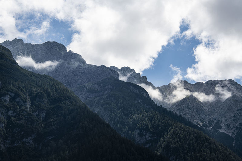 High mountains covered by forest touch the blue cloudy sky