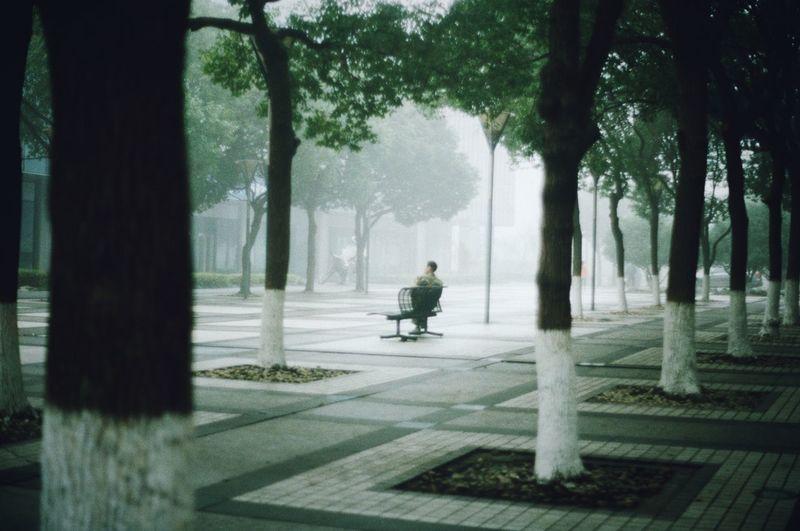 Man walking on footpath by street in city