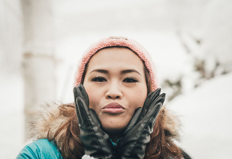Portrait Of Woman Wearing Warm Clothing Blowing Kiss During Winter