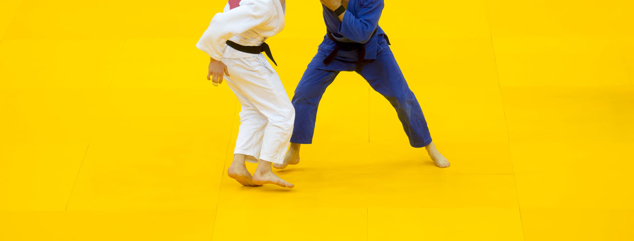 Two judo fighters in white and blue uniform. Action Kick Fitness Game Judo Dojo Fu Kung Karate Martial Fight Taekwondo Kimono Sport Jujitsu Japanese  Uniform Man Aïkido Belt  Athlete White Combat Exercise Competition Practice Isolated Strong Active Defense Adult Arts Strength Two Power Lifestyle Activity Healthy Skill  Attack Pose Traditional Caucasian Young Indoors  Throw Symbol Yellow Colored Background Studio Shot Low Section People Yellow Background Human Body Part Casual Clothing Clothing Shoe Body Part Men Human Leg Full Length Standing Business Males  Human Limb Jeans