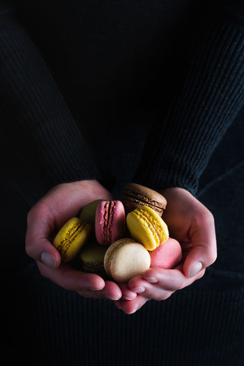 Macarons and hands   food photography Human Hand Hand One Person Holding Food Human Body Part Food And Drink Black Background Close-up Real People Unrecognizable Person Snack Macarons Macaroon Different Colors French Food Food Photography Foodphotography Sweet Food The Week on EyeEm Light And Shadow Nikonphotographer